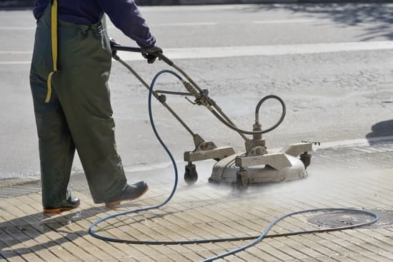 Worker in Orlando doing commercial pressure washing on parking lot.