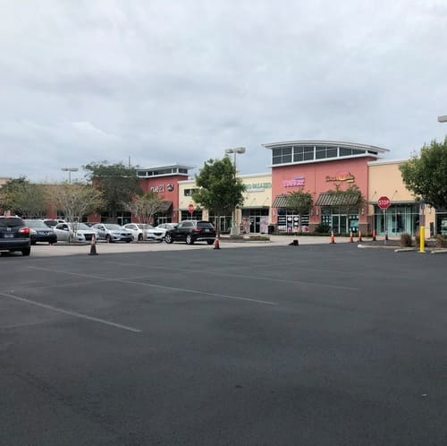 A view of the parking lot at Posner Commons Shopping Center before D & C Parking Lot Maintenance enhanced it